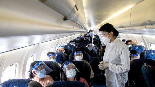 Una azafata de Buddha Air viste un traje protector y una máscara durante un simulacro de ...