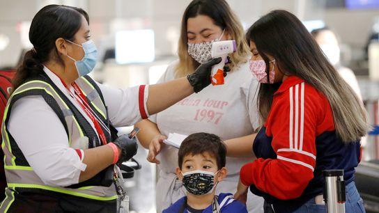 Viajar en avión implica el riesgo de exponerse al coronavirus. En la foto, le toman la temperatura ...