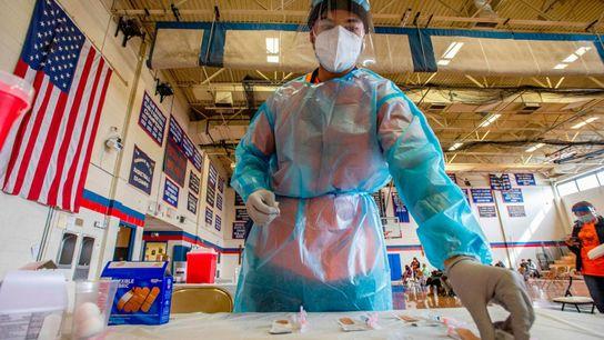 Elvin Toro, de 26 años, exmédico de las fuerzas armadas, organiza las jeringas antes de aplicarle ...