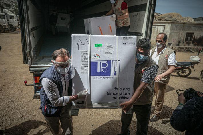 Trabajadores en Idlib, Siria, descargan más de 50.000 dosis de vacunas contra la COVID-19 el 21 ...