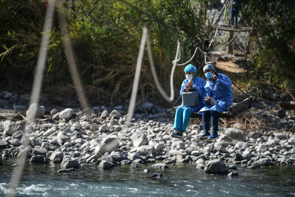 Los trabajadores de la salud se sientan en una plataforma mientras cruzan la parte Camaná del ...