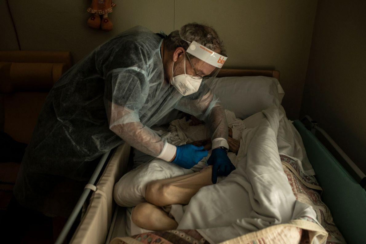 Una enfermera vacuna a una anciana enferma en su habitación de un hogar de ancianos en ...