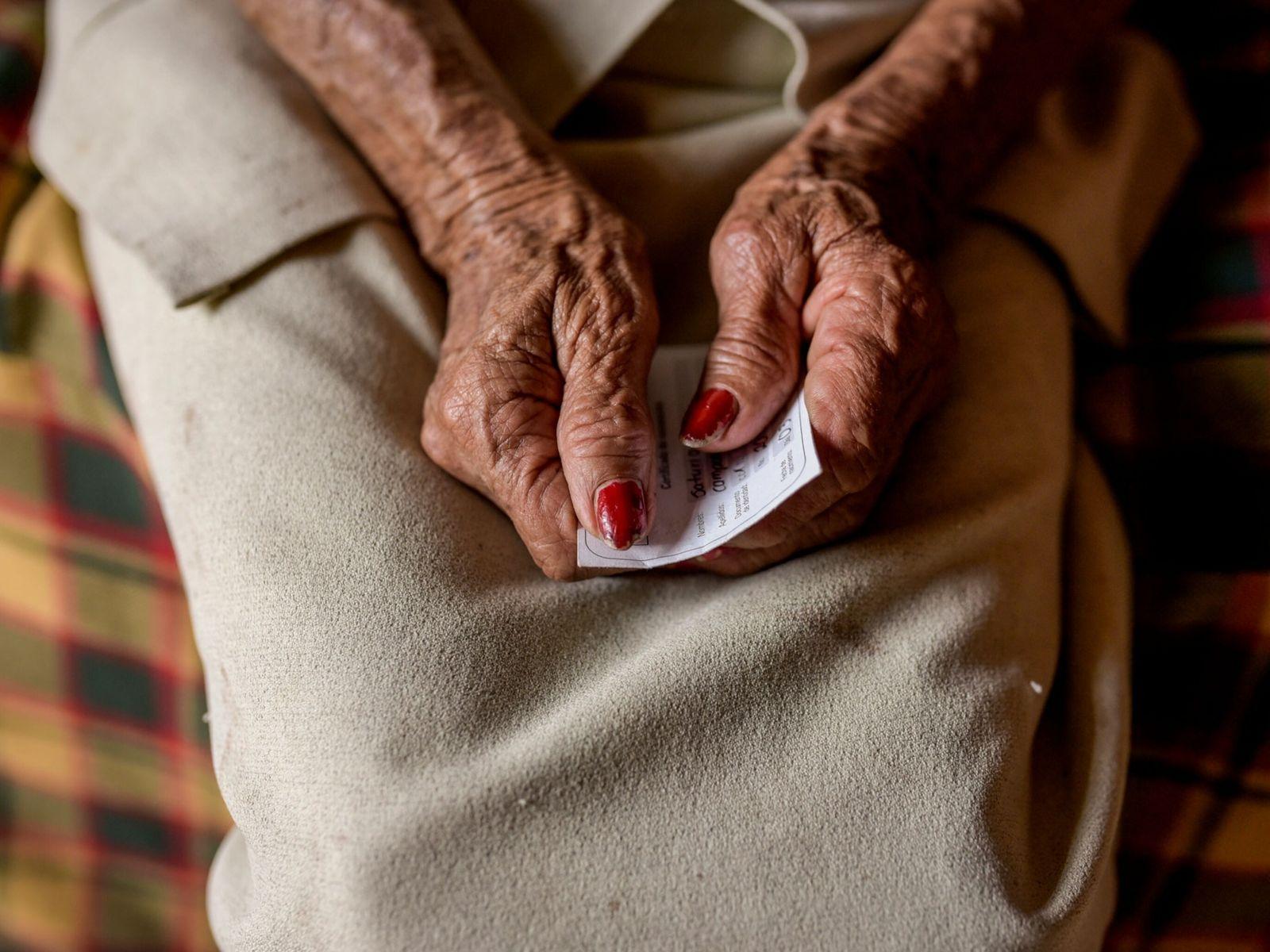 Saturia Campos, de 80 años, agarra su carnet de vacunación después de que una campaña de ...