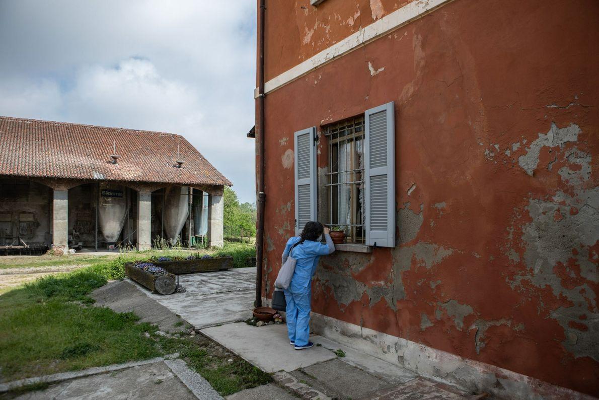 Una enfermera mira por la ventana de una granja durante una campaña de vacunación puerta a ...