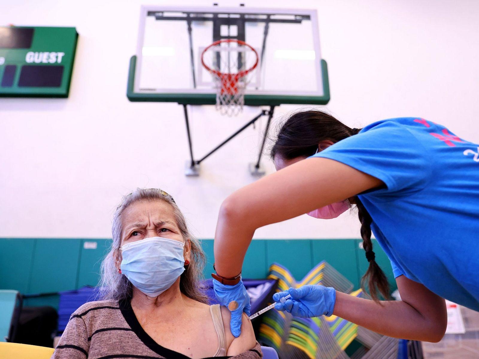 La enfermera Darryl Hana aplica una dosis de la vacuna de Pfizer para la COVID-19 a ...