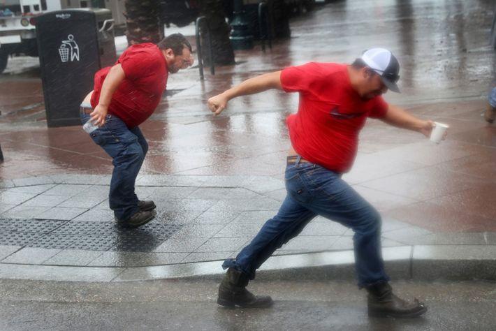 Los trabajadores de servicios públicos luchan contra el viento del huracán Ida mientras esperan que pase ...