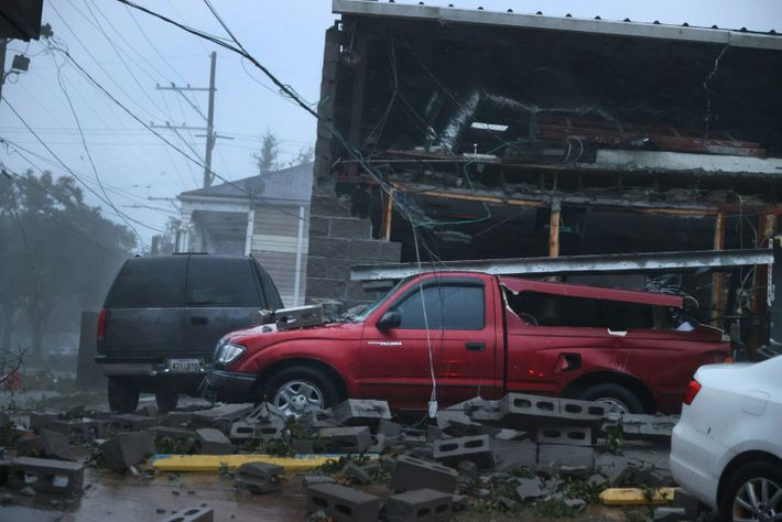 Los vehículos resultan dañados después de que el frente de un edificio colapsara durante el huracán ...
