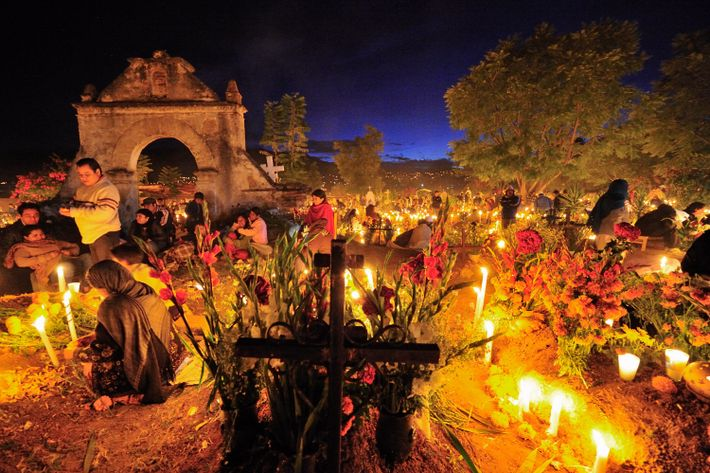 Las flores y las velas crean el ambiente durante una vigilia del Día de los Muertos ...
