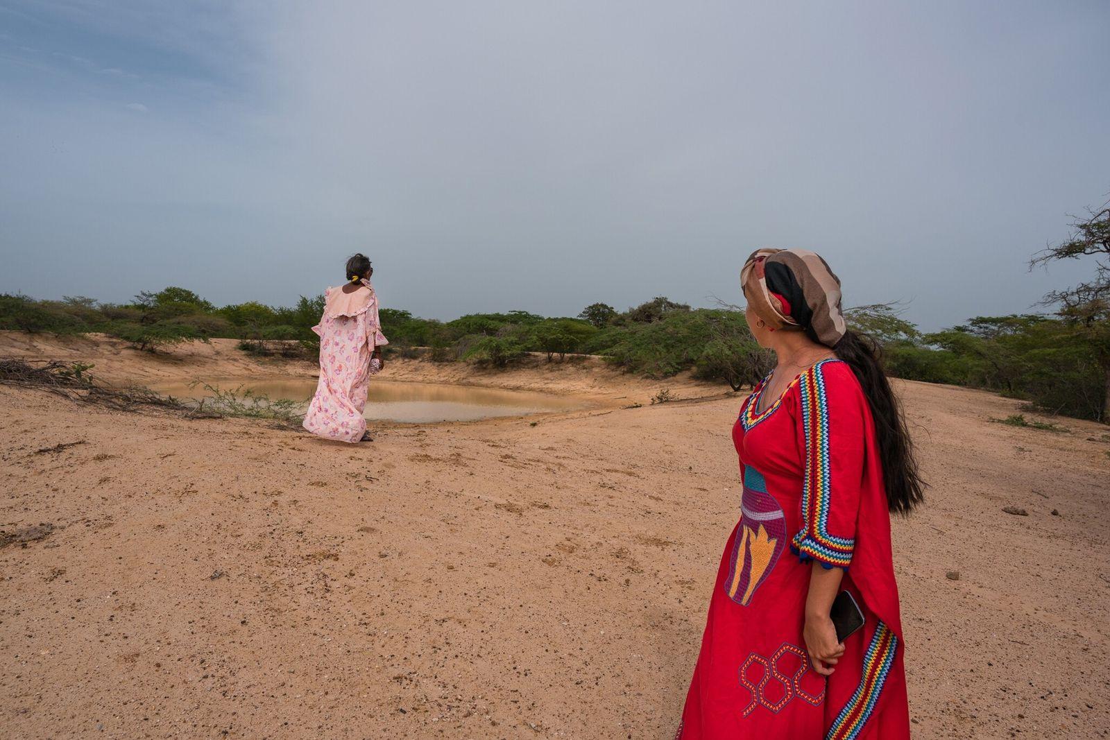 Celia Vangrieken y Yadira Martinez miran un estanque que proporciona agua limitada a una comunidad Wayuu ...