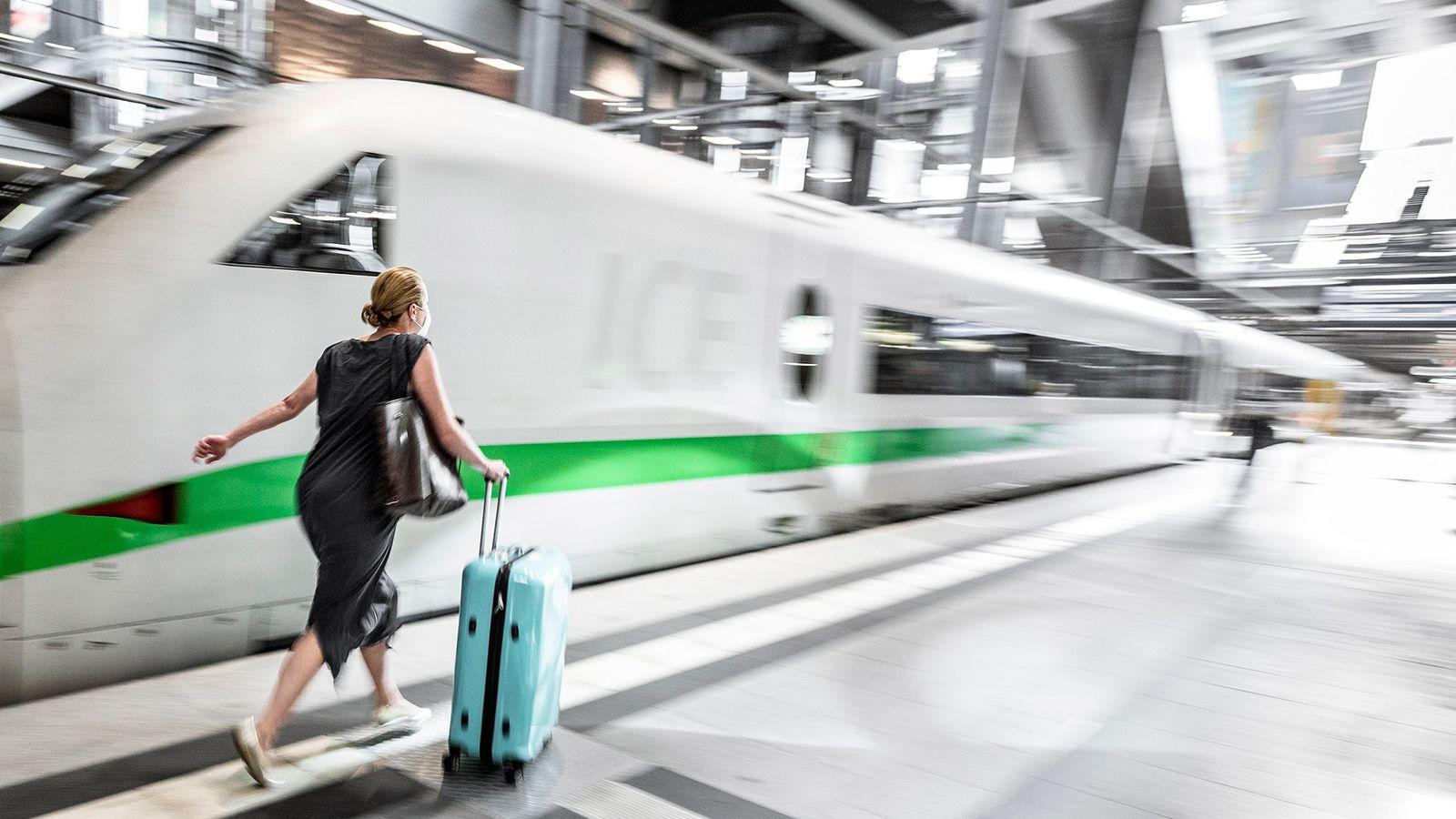 Una pasajera se apura para poder tomar el tren England Intercity Express en la estación central ...