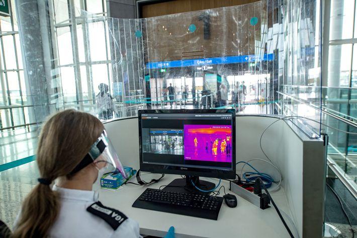 Un oficial de seguridad del aeropuerto de Estambul utiliza un escáner de temperatura térmica para escanear ...