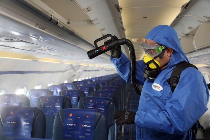 Un trabajador con equipo de protección desinfecta un avión de Asrair Airlines en el Aeropuerto Internacional ...