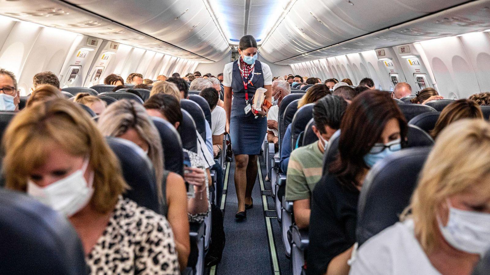 Pasajeros con mascarillas en uno de los primeros vuelos entre Ámsterdam, Países Bajos y Burgas, Bulgaria ...
