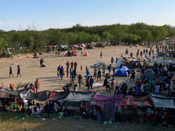 People seeking asylum wait to turn themselves in to Border Patrol agents, near the Del Rio ...