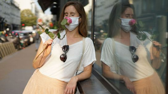 Una mujer con una mascarilla protectora huele una rosa mientras deambula por las calles de París