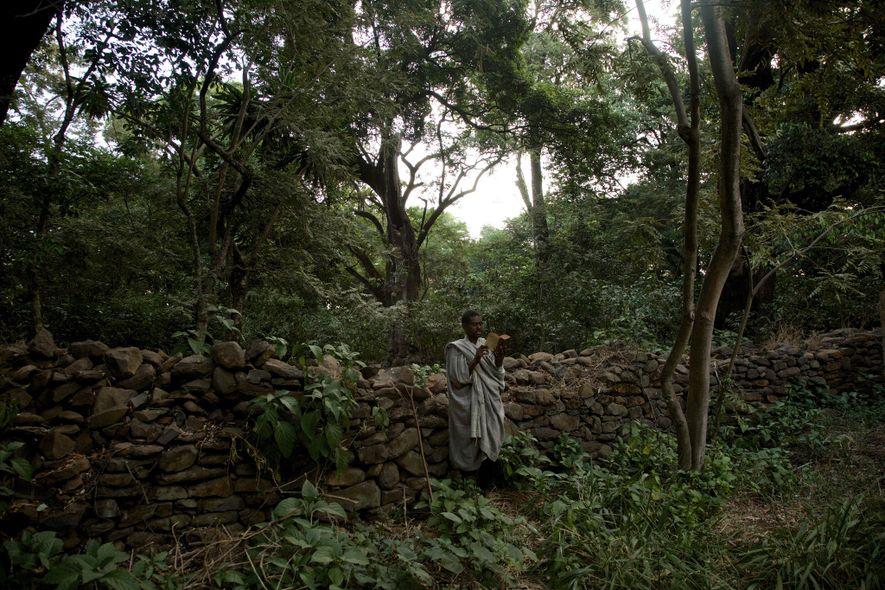 Un hombre reza y lee la sagrada escritura en el patio de la iglesia de Robit ...
