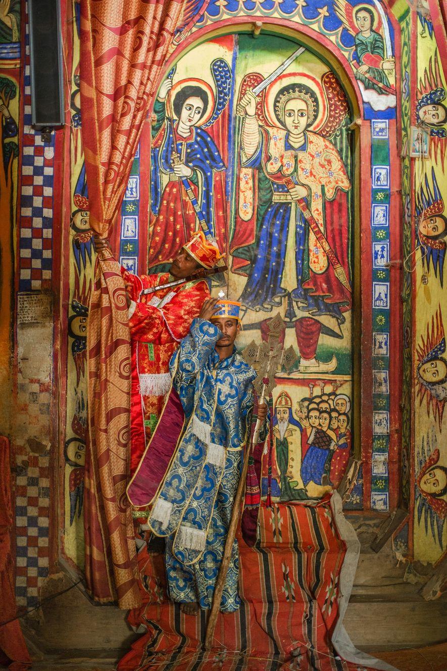 Un sacerdote vestido con túnicas ceremoniales frente a un mural de vivos colores en la iglesia ...