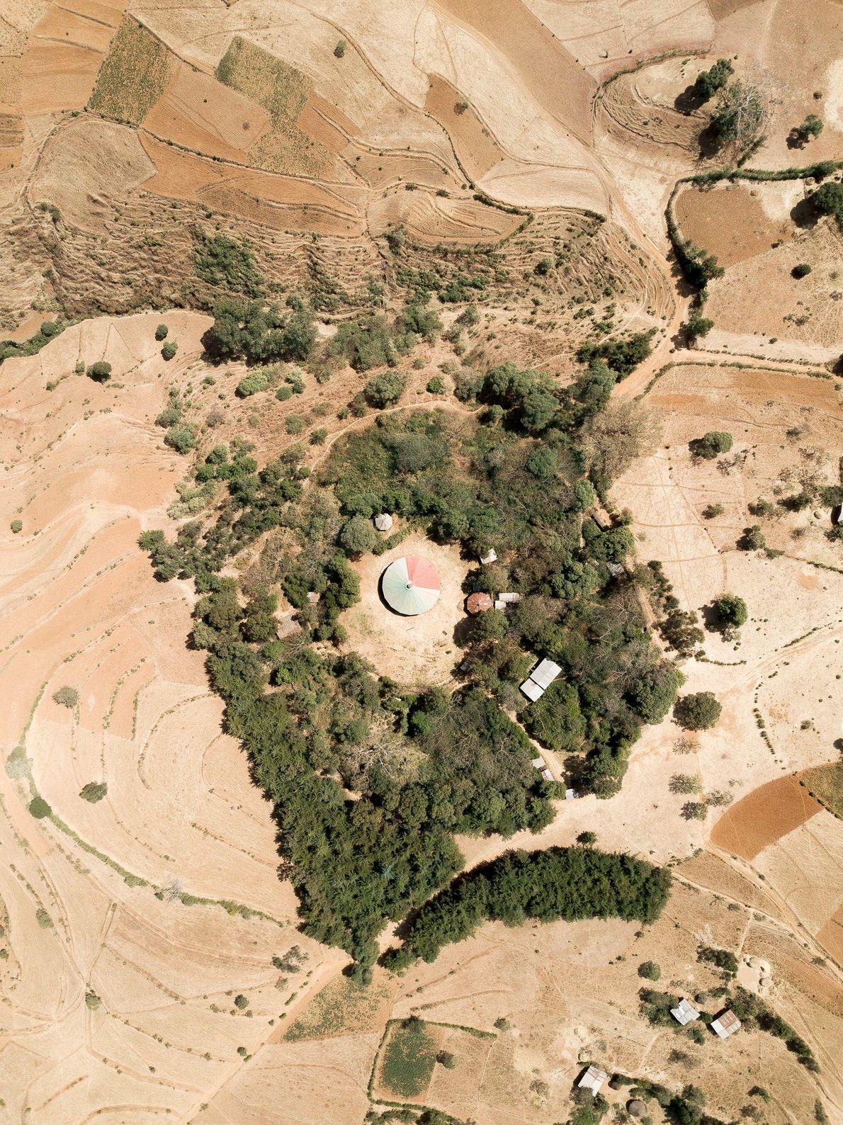 Varias construcciones auxiliares se ubican en el bosque junto a la iglesia Tebebari Michael en Anbesame, ...
