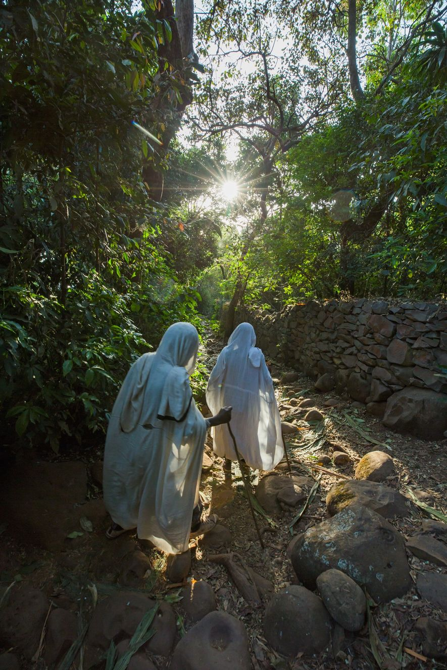 Dos mujeres caminan por el bosque de la iglesia de Betre Mariam cerca de Zege.