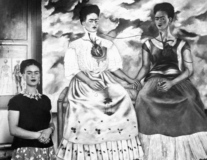 """Frida Kahlo junto a su cuadro, titulado """"Las dos Fridas"""", en 1939."""