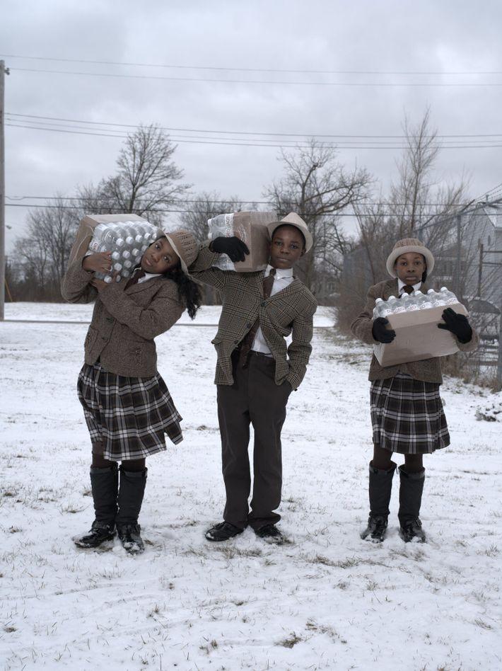 2016   Los hermanos Julie, Antonio e India Abron recolectan su ración diaria de agua de la Estación de Bomberos ...