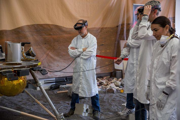 El investigador principal de InSight, Bruce Banerdt (centro) se encuentra con la réplica de la nave ...