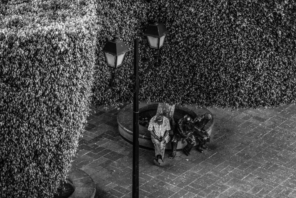 Un hombre descansa junto a dos esculturas durante la cuarentena del COVID-19 en Querétaro, México el ...