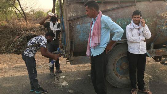 Los compañeros de caminata de Paul Salopek, Verinder Singh (izquierda) y Siddharth Agarwal (atrás, bebiendo), beben ...