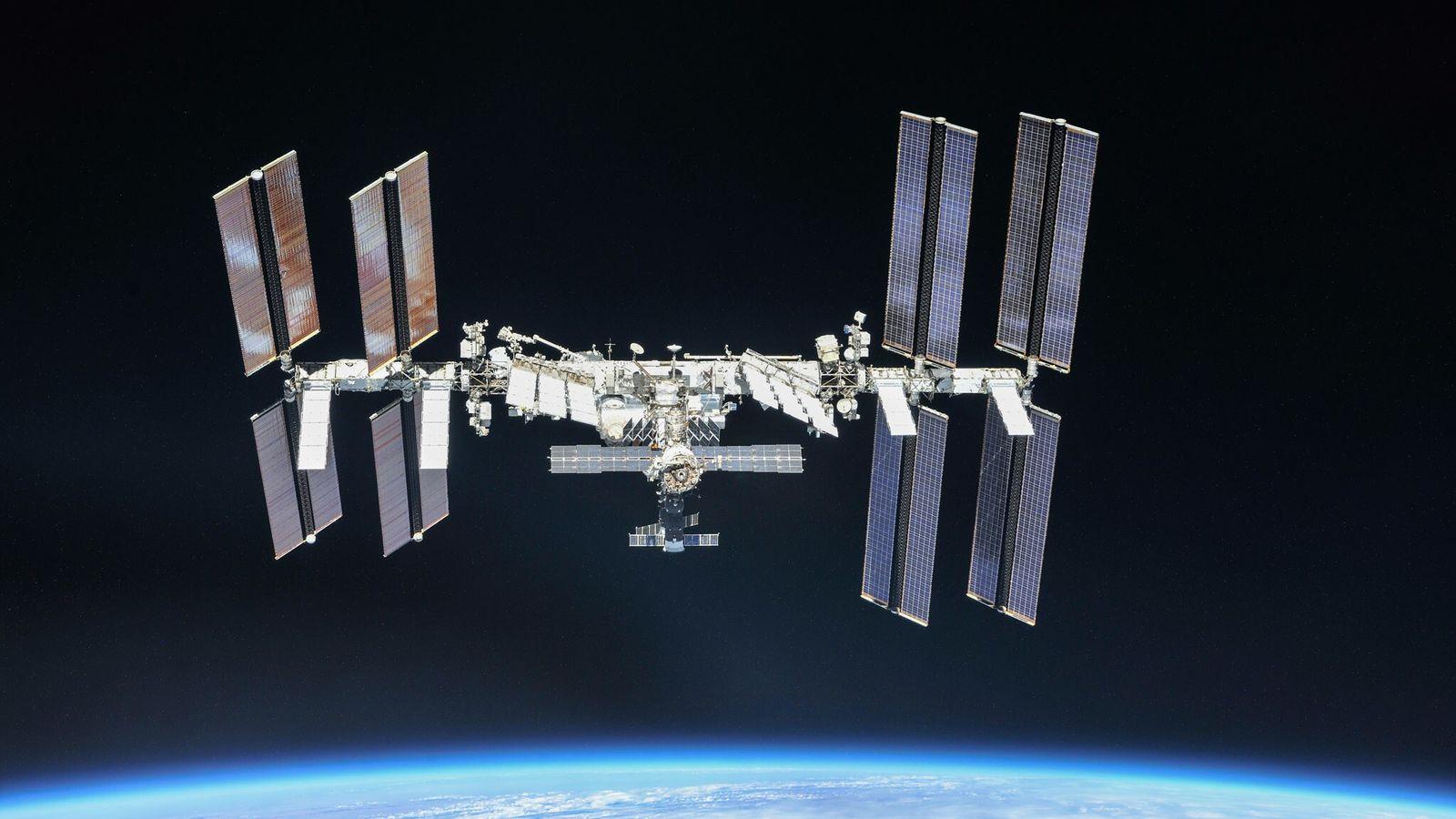Flotando sobre la Tierra y sobre su fina atmósfera azul, la Estación Espacial Internacional ocupa un ...