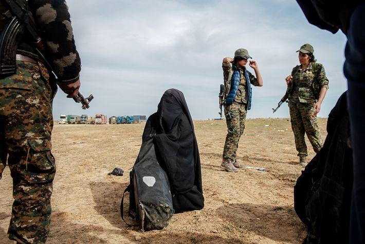 Las soldados kurdas rodean a una mujer que se rinde mientras el Estado Islámico abandona la ...