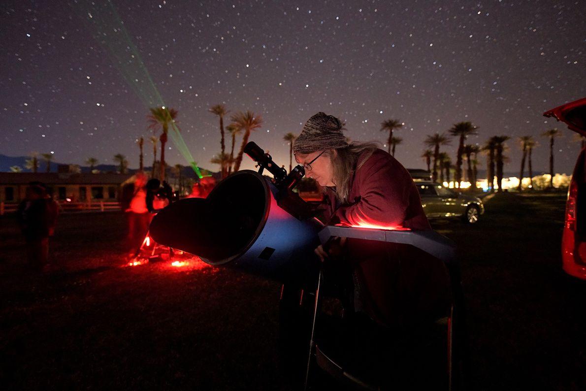 Cheryl Wilcox de Riverside Astronomical Society apunta su telescopio hacia los campos de estrellas que brillan ...