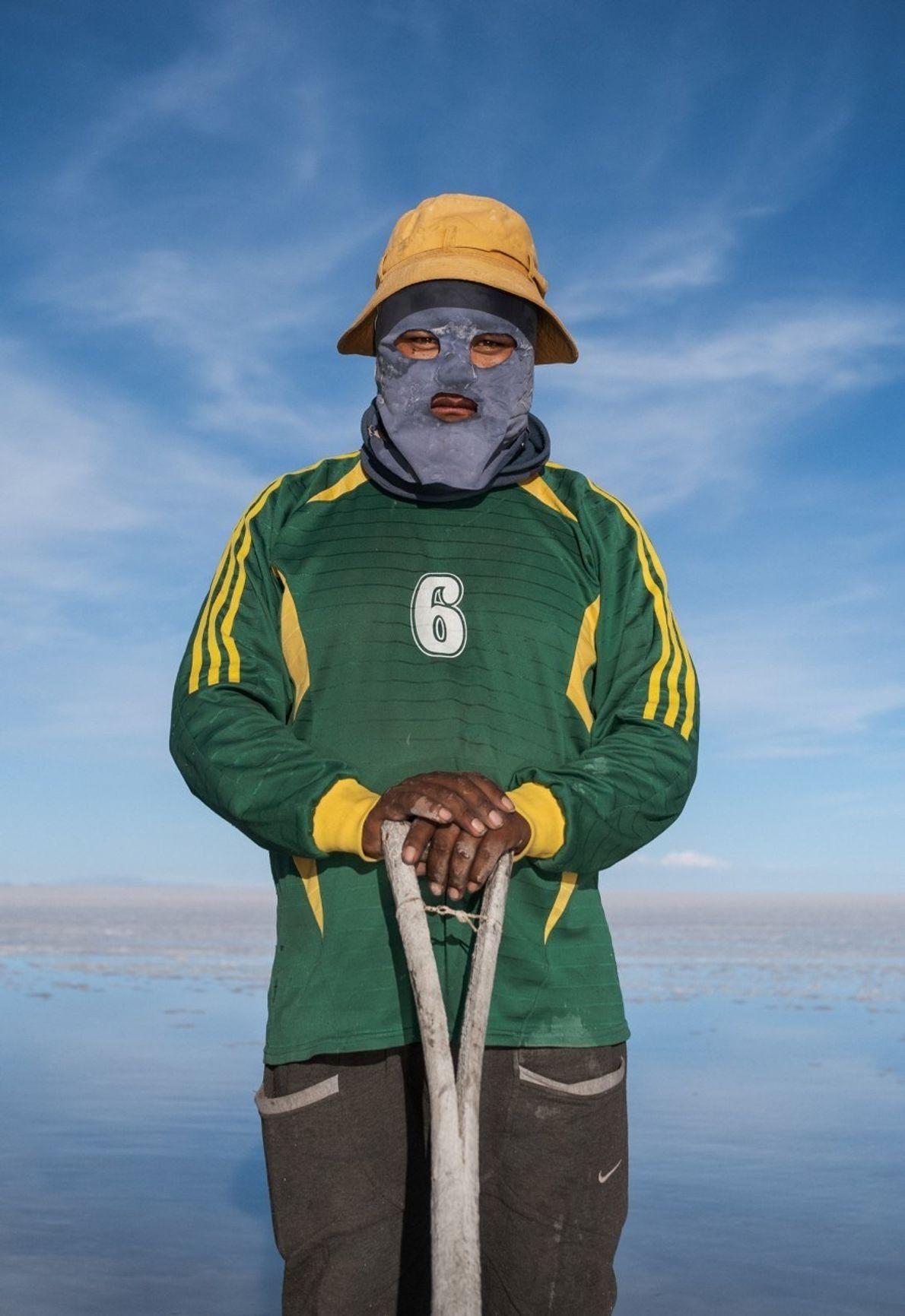 Wilmer Flores, con la cara cubierta para no quemarse con el sol, recoge sal cerca del ...
