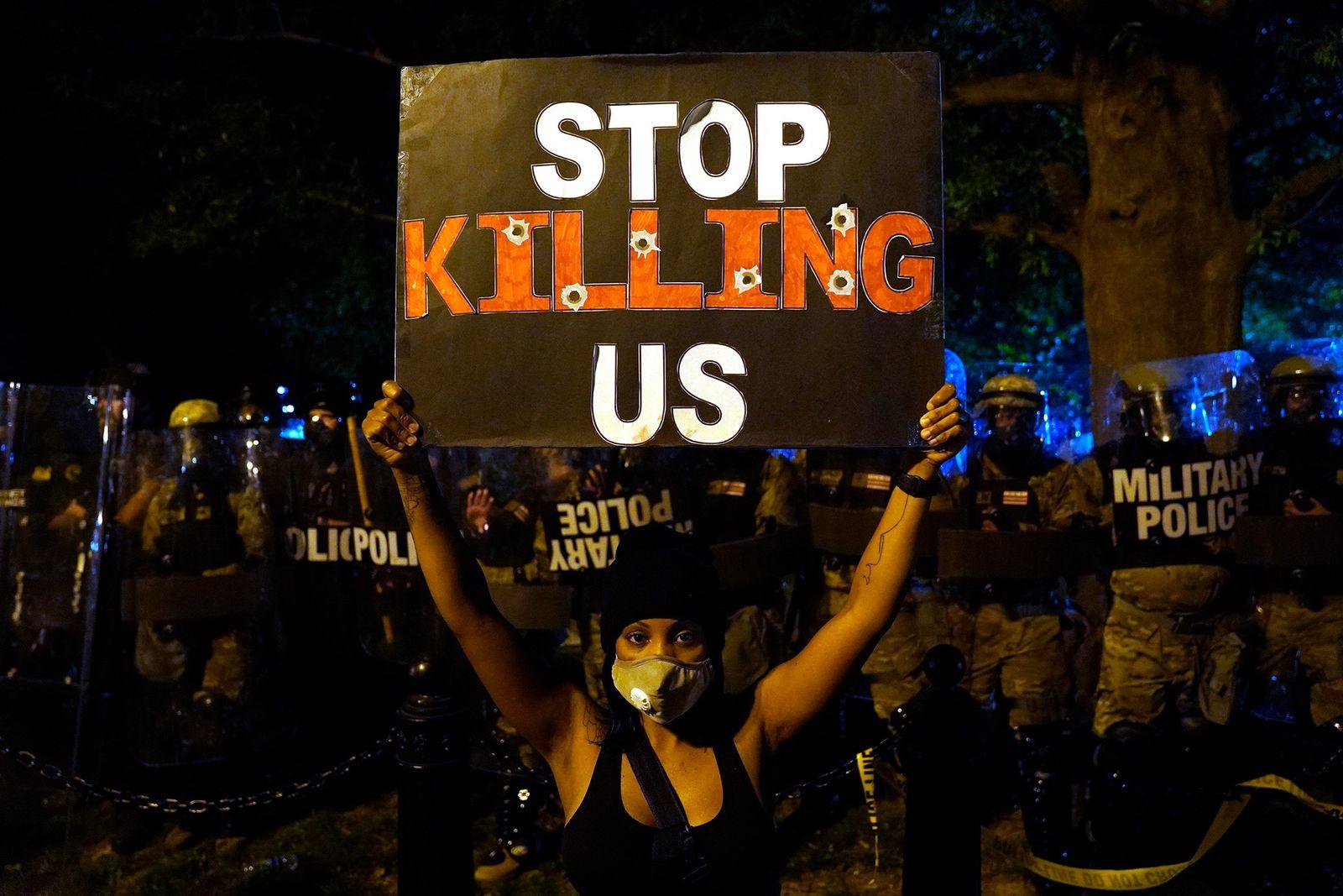 Una manifestante sostiene un cartel durante una protesta frente a la Casa Blanca, donde cientos de ...