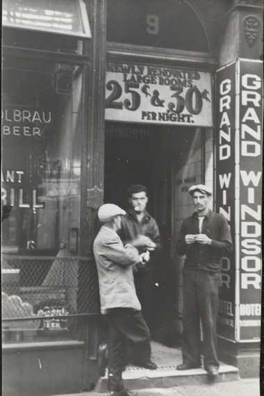 [Destitute men in front of flophouse.]