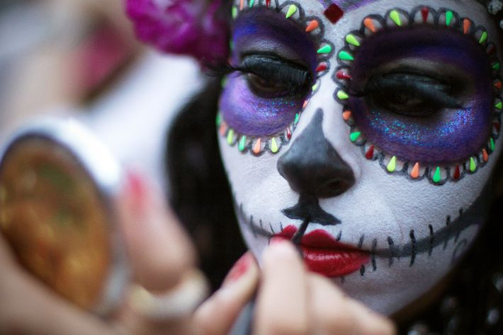 A woman adds finishing touches on her Catrina makeup ahead of the Catrinas Parade in Mexico ...