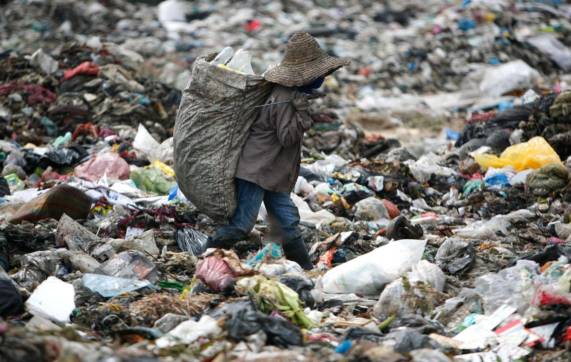 Un hombre busca plástico para reciclar en un sitio de basura en Malasia.