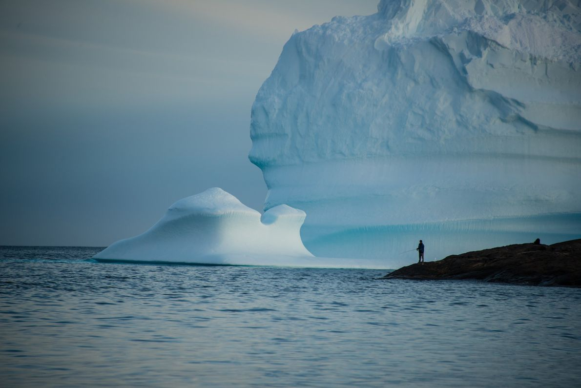 Un pescador lanza una línea frente a la costa sureste de Groenlandia. Los ríos y lagos ...
