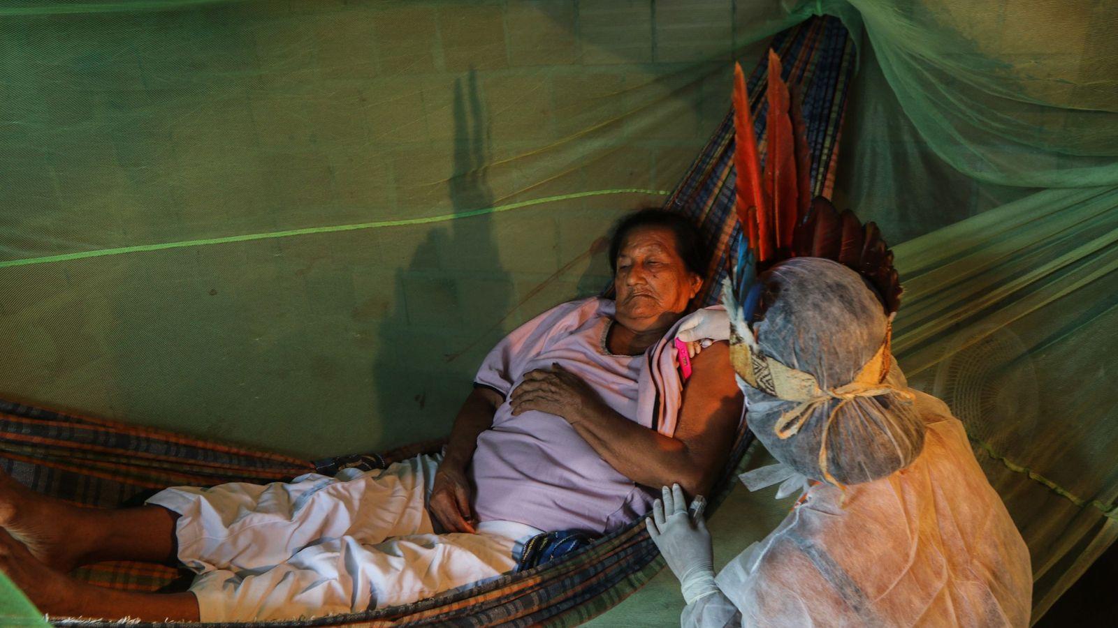 Vanda Ortega asiste a Carolina Miguel, una indígena Baniwa de 85 años. La paciente tenía síntomas graves ...