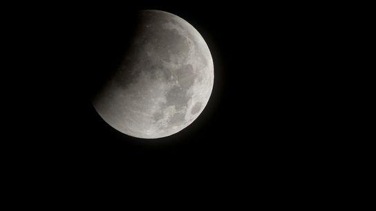 La sombra de la Tierra oscurece la Luna en el comienzo de un eclipse total lunar ...