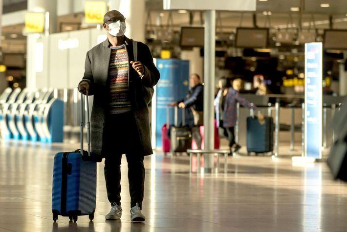 En el aeropuerto de Bruselas, un hombre lleva una mascarilla durante el brote de coronavirus.
