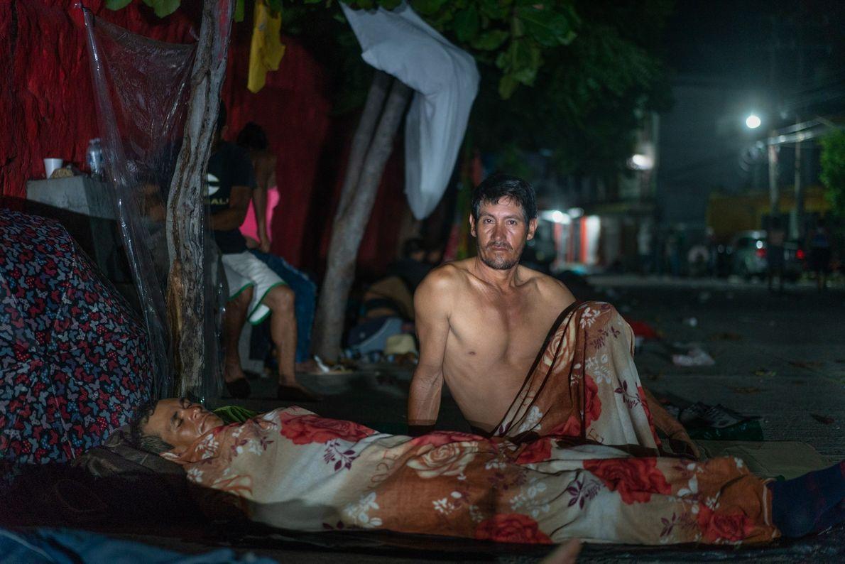 Los migrantes duermen al aire libre en el patio de una casa en el pueblo de ...