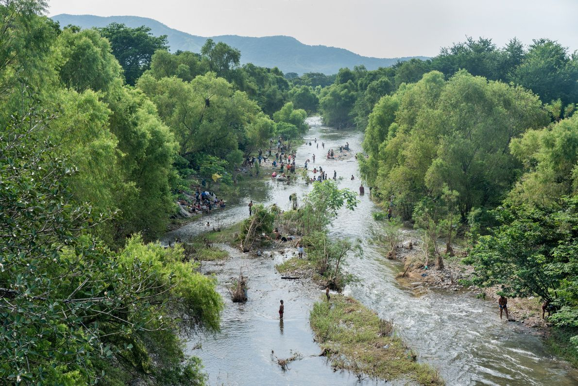 Cientos de migrantes centroamericanos se refrescan, se bañan y lavan su ropa en el río Novillero, ...