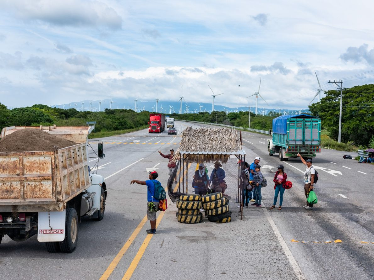 Migrantes hondureños esperan a que les den un aventón al lado de la carretera cerca del ...