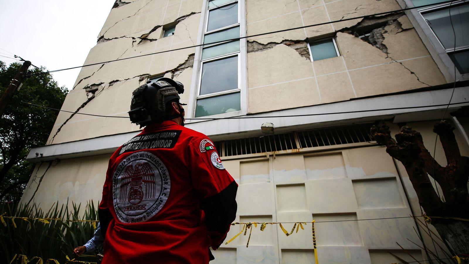 Un trabajador de búsqueda y rescate urbano en la Ciudad de México observa un edificio dañado ...