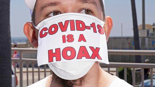 """Un manifestante en un encuentro """"antibloqueo"""" en Huntington Beach, California, el 1 de mayo de 2020. Su ..."""