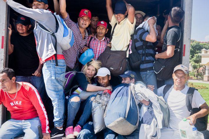 Migrantes salvadoreños se amontonan dentro de un camión acoplado que los había recogido para llevarlos a ...