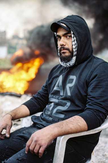Mahmoud Jaloul, de 30 años, se sienta frente a unos neumáticos en llamas que bloquean una ...
