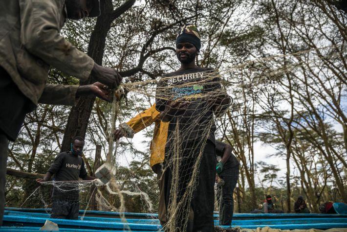 Los pescadores desenredan las redes en la playa Karagita en el lago.