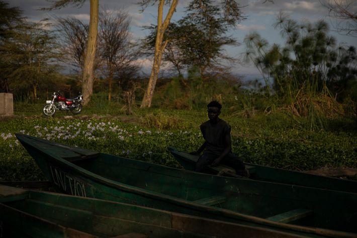 Un hombre se sienta en un barco pesquero en la playa Tarambeta. La vegetación detrás de ...