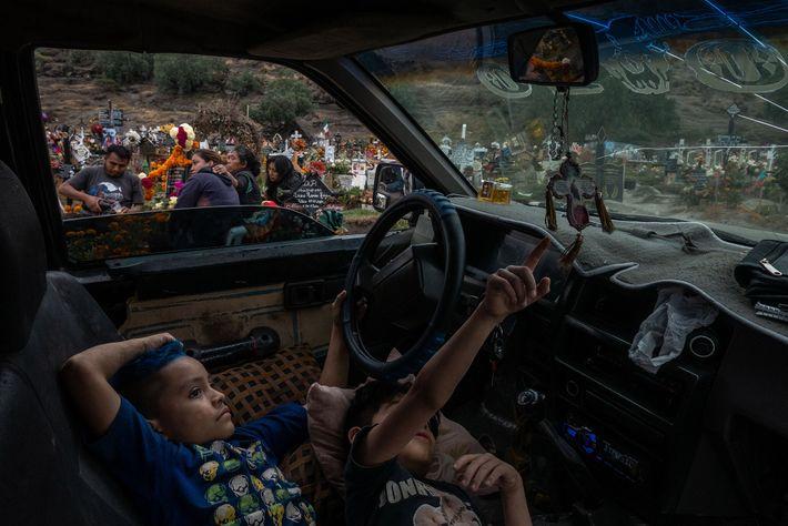 Andres y Alan esperan dentro de su camioneta mientras su familia lamenta la muerte de su ...